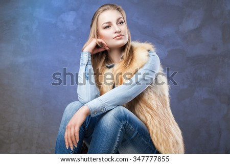 Portrait of elegant woman sits wearing blue jeans and fur vest over blue background - stock photo