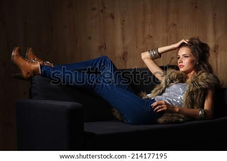 Portrait of elegant woman sitting on black sofa wearing a blue - stock photo