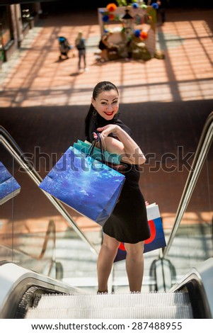 Portrait of elegant woman with shopping bags standing on escalator at mall