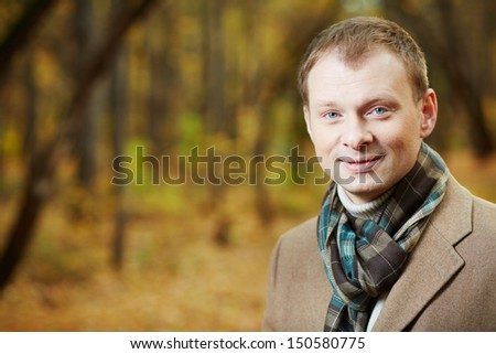 Portrait of elegant young man wearing coat and scarf - stock photo