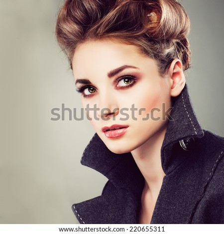 Portrait of elegant young woman in a grey overcoat  on a grey background - stock photo