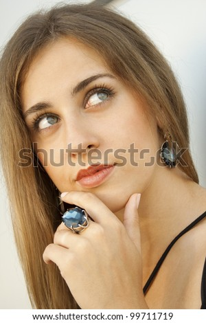 Portrait of elegantly beautiful woman covers her mouth with his hand. The girl beautiful jewelry, ring and earrings with large blue stones - stock photo