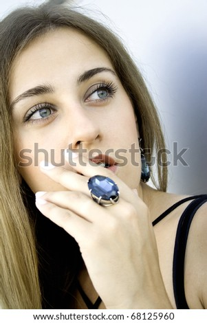 Portrait of elegantly beautiful young woman covers her mouth with his hand. The girl beautiful jewelry, ring and earrings with large blue stones - stock photo