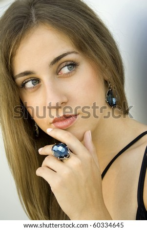 Portrait of elegantly beautiful young woman. The girl beautiful jewelry, ring and earrings with large blue stones