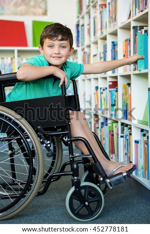 Portrait of elementary handicapped boy searching books at library in school