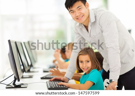 portrait of elementary school computer teacher and students in computer room - stock photo