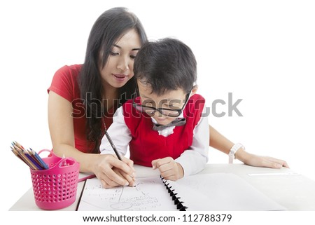 Portrait of elementary school student learn to write with his mother - stock photo