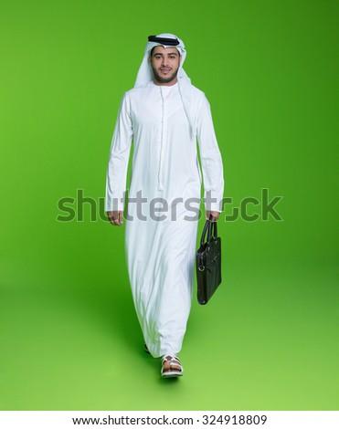 Portrait of Emirati businessman carrying bag - stock photo