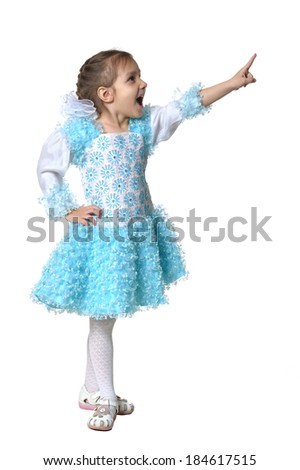 Portrait of emotional little girl in blue dress pointing on white background - stock photo