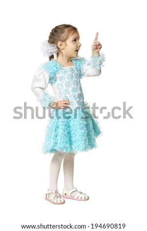 Portrait of emotional little girl in blue dress pointing up on a white background - stock photo