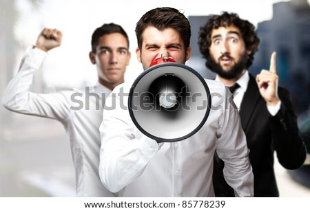 portrait of employees group shouting using a megaphone against a city background - stock photo