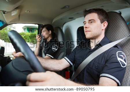 Portrait of EMS worker driving ambulance while team member talks with dispatcher - stock photo