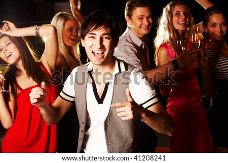 Portrait of energetic male dancing on background of happy friends