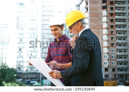Portrait of engineer and builder. Men with helmets standing near new unfinished construction and discussing graphics and blueprints
