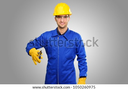 Portrait Of Engineer Holding Plier On Grey Background