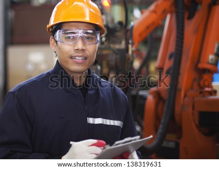 Portrait of engineer writing on a clipboard in a factory - stock photo