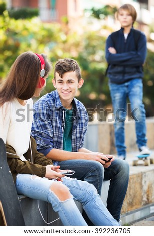 Portrait of envy male teen standing aside of girlfriend talking with boy - stock photo