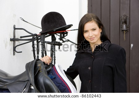 portrait of equestrian with saddle - stock photo