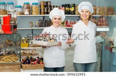 Portrait of european female baker with pastry smiling in bakery - stock photo