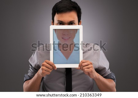 Portrait of evil man with half of his face covered by digital tablet with an image on happy smile: hypocrisy in the internet concept - stock photo