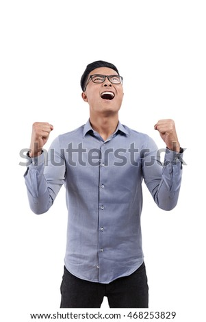 Portrait of excited Asian man holding hands folded in elbows and screaming in joy against white background. Concept of success