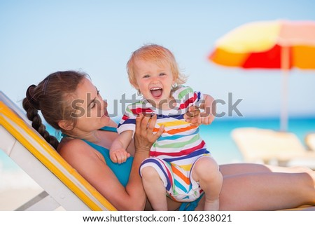 Portrait of excited baby with mother on beach - stock photo