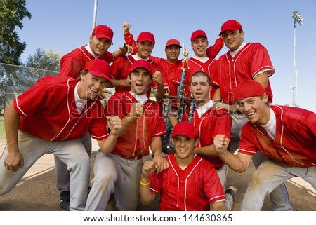 Portrait of excited baseball team holding trophy with pride - stock photo