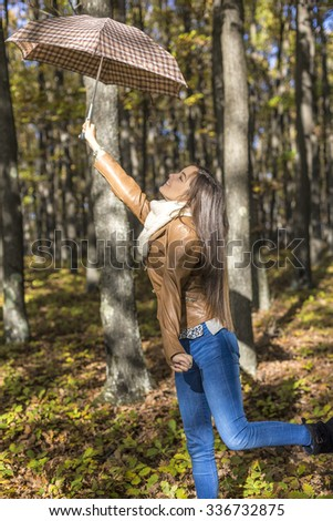 Portrait of excited beautiful teenage girl  holding an umbrella in the forest  - stock photo