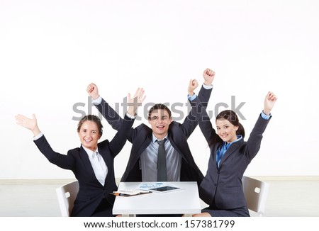 Portrait of excited business partners looking at camera at workplace