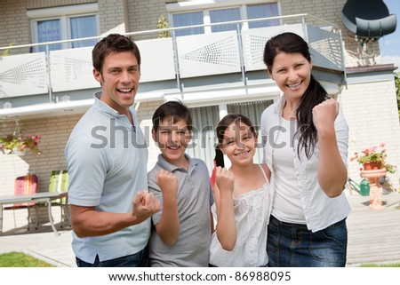 Portrait of excited family celebrating success in front of their home - stock photo