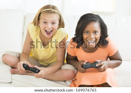 Portrait of excited female friends playing video games at home - stock photo