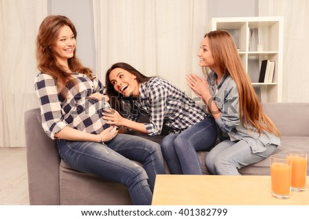 Portrait of excited girls listening to tummy of their pregnant friend - stock photo
