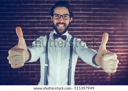 Portrait of excited man with thumbs up gesture against brick wall - stock photo