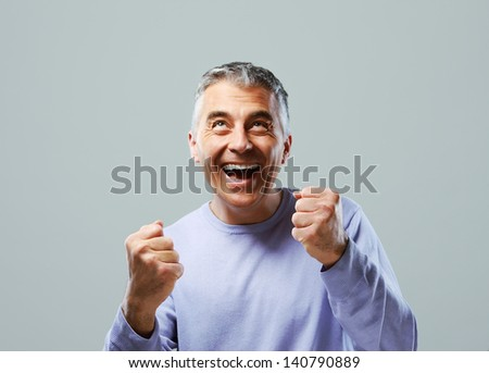 Portrait of excited mature man, raising his fists on grey background. - stock photo