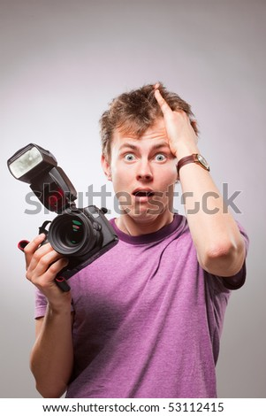 Portrait of excited surprised photographer with camera at hand - stock photo