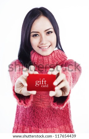 Portrait of excited woman wearing red sweater and showing a red gift card. isolated on white - stock photo