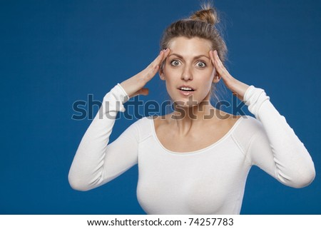 Portrait of excited young female holding her head - stock photo
