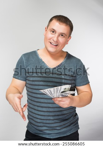Portrait of excited young man clenching fist while holding US currency