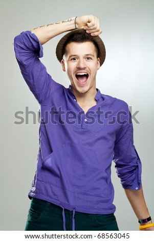 Portrait of excited young man wearing a hat celebrating success - stock photo
