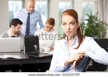 Portrait of executive business woman sitting at office while her financial team working at background with laptop. Teamwork at office.
