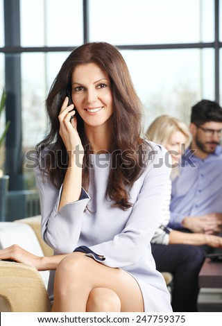 Portrait of executive business woman smiling during a telephone conversation while sitting at meeting.