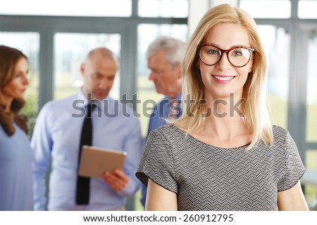 Portrait of executive business woman standing at meeting while her colleagues consulting at background. Business people. - stock photo