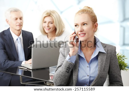 Portrait of executive business woman using her mobile while business team working with laptop at background.  - stock photo