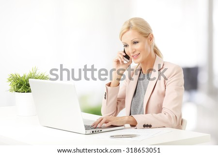 Portrait of executive businesswoman making call while sitting at office in front of computer and working. - stock photo