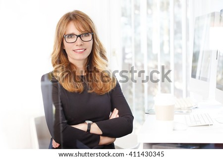 Portrait of executive businesswoman sitting at her workplace while looking at camera and smiling. - stock photo