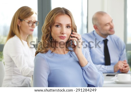 Portrait of executive businesswoman sitting at office and making call while business people consulting at background.