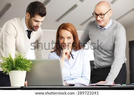 Portrait of executive businesswoman sitting in front of computer with sales men and working on new project.  - stock photo