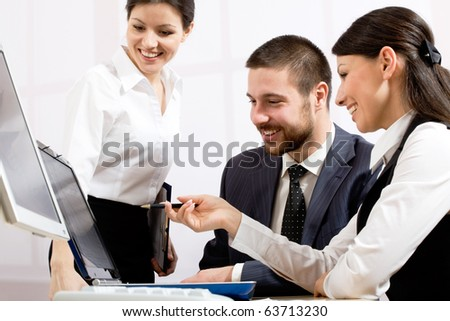 Portrait of executive employees looking at laptop monitor and discussing new project - stock photo