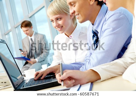 Portrait of executive employees looking at laptop monitor in office and interacting