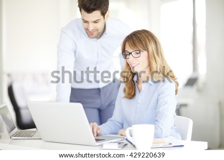 Portrait of executive financial businesswoman and her young assistant using laptop while discussing the new business plan.